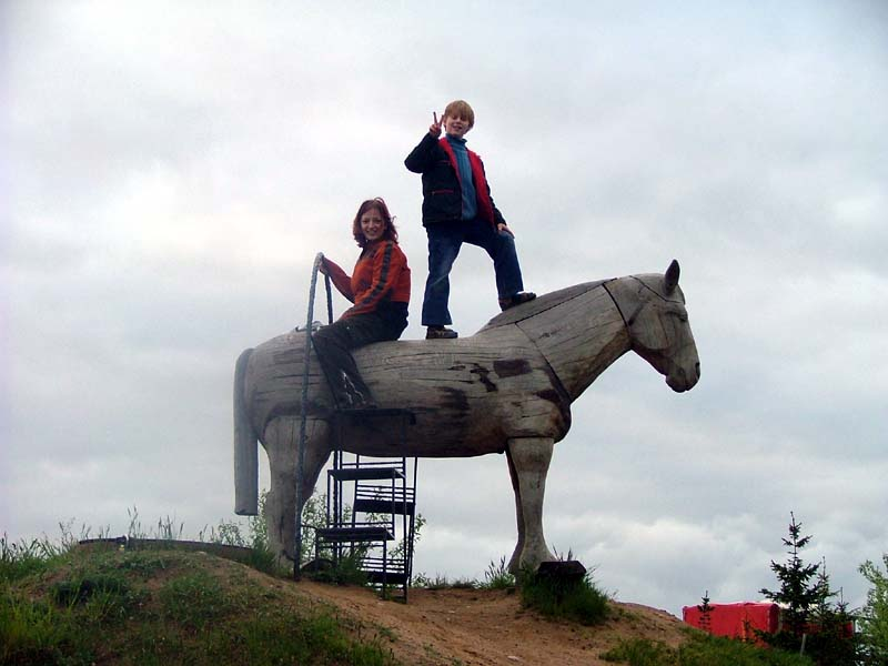 My sister M with nephew J on a wooden horse.
