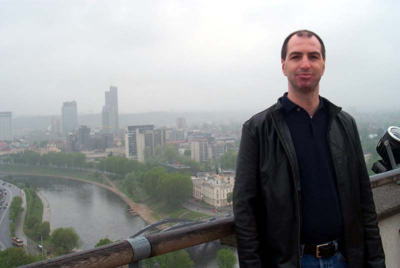 S on the observation deck at the top of the Vilnius castle, with some of the Vilnius newer neighborhoods and the Neris river visible behind him (May 2004)