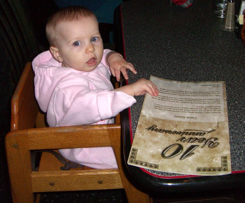 E in a high chair with a menu, December 2005