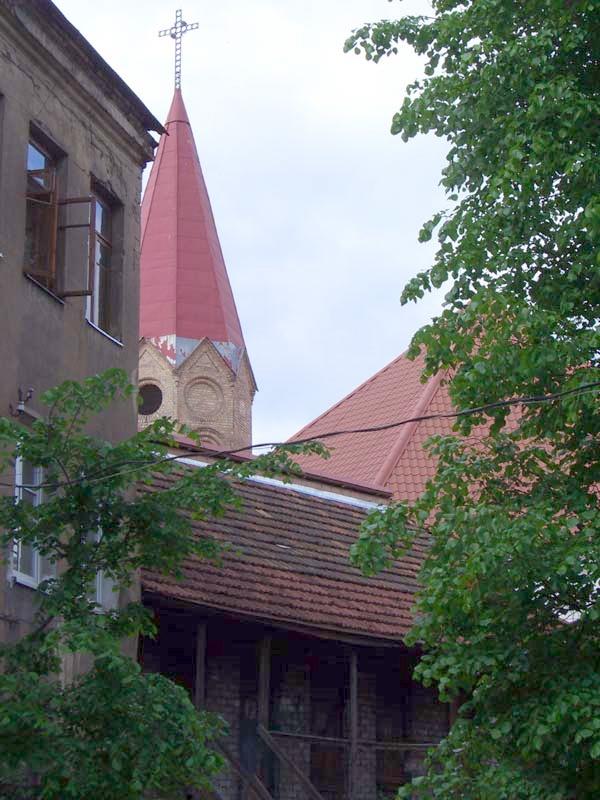 A church steeple behind storage buildings