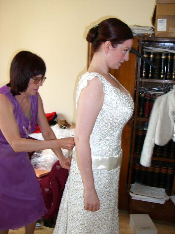 Mom zips up the dress for M