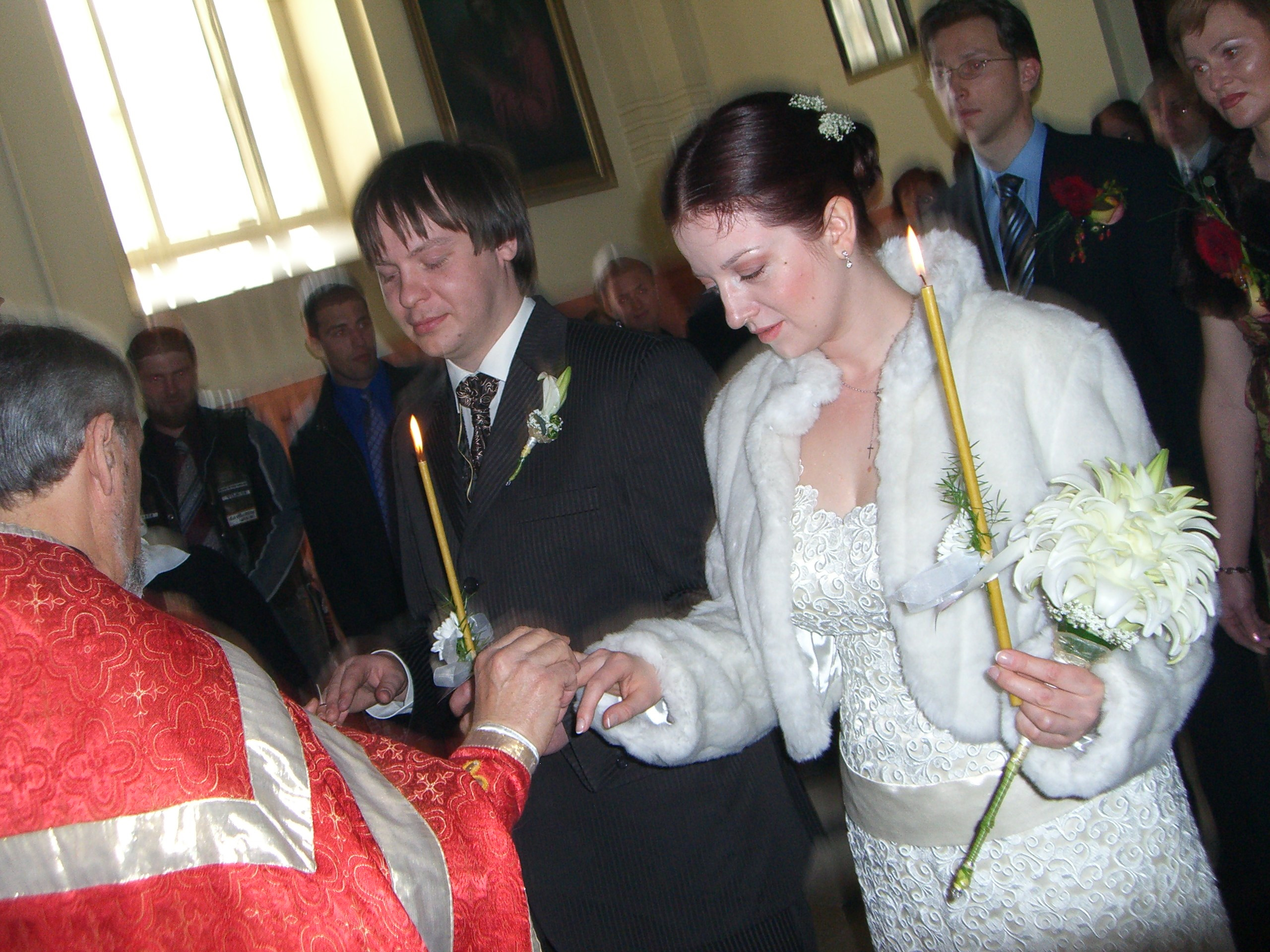 The priest puts rings on the bride's and groom's hands