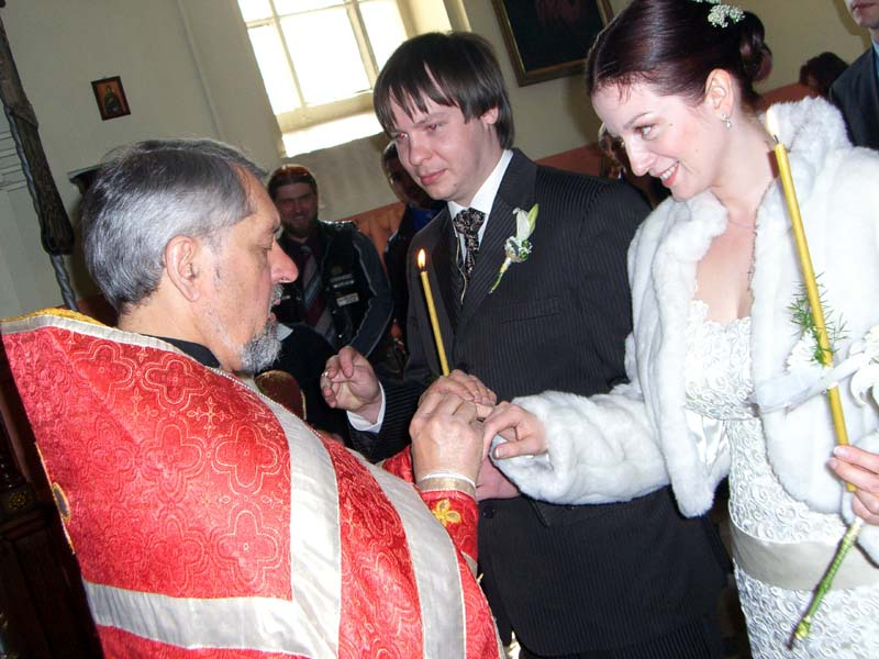 The priest puts a ring on the bride's hand