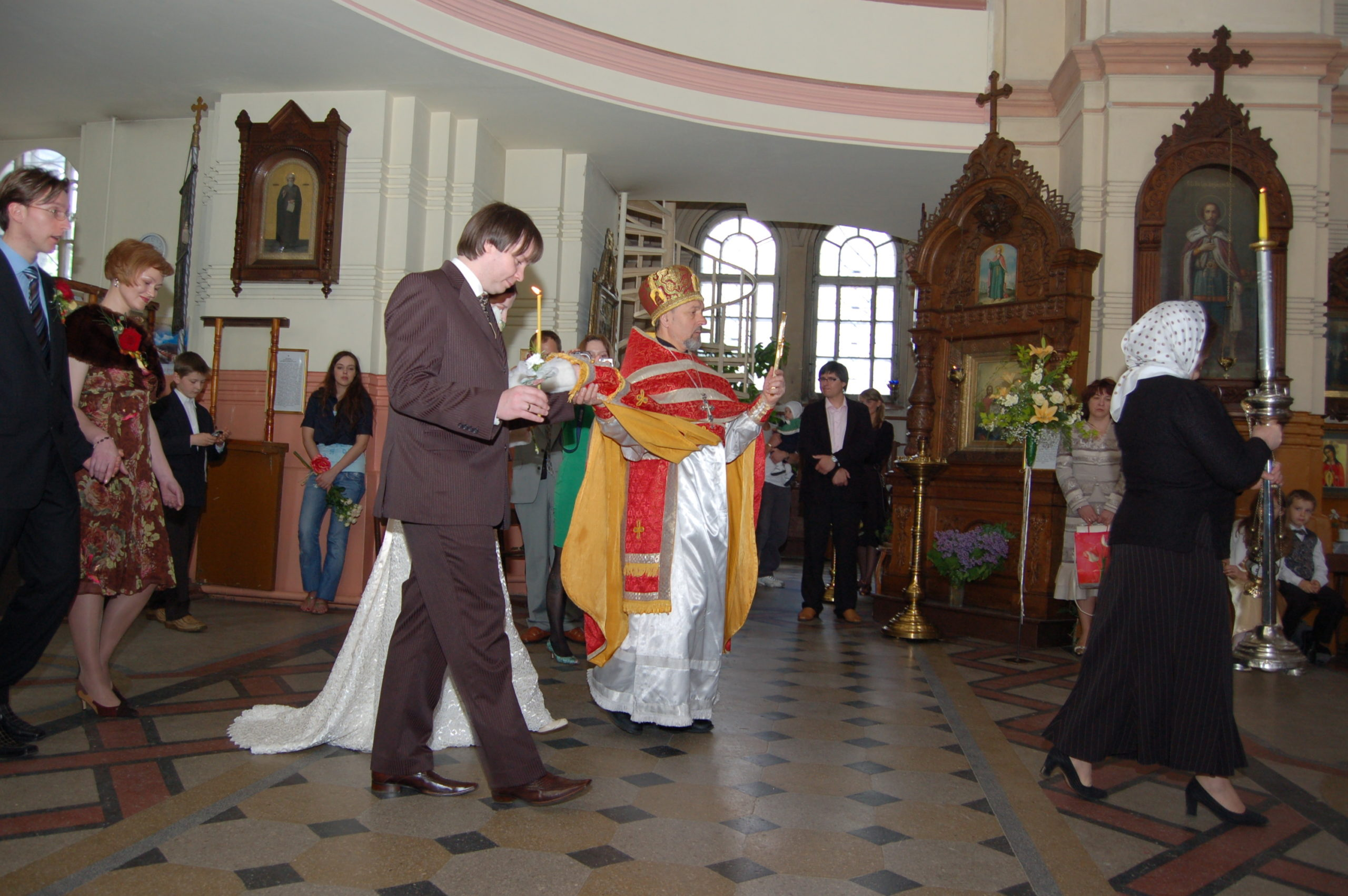 Priest leads the bride and groom towards the altar