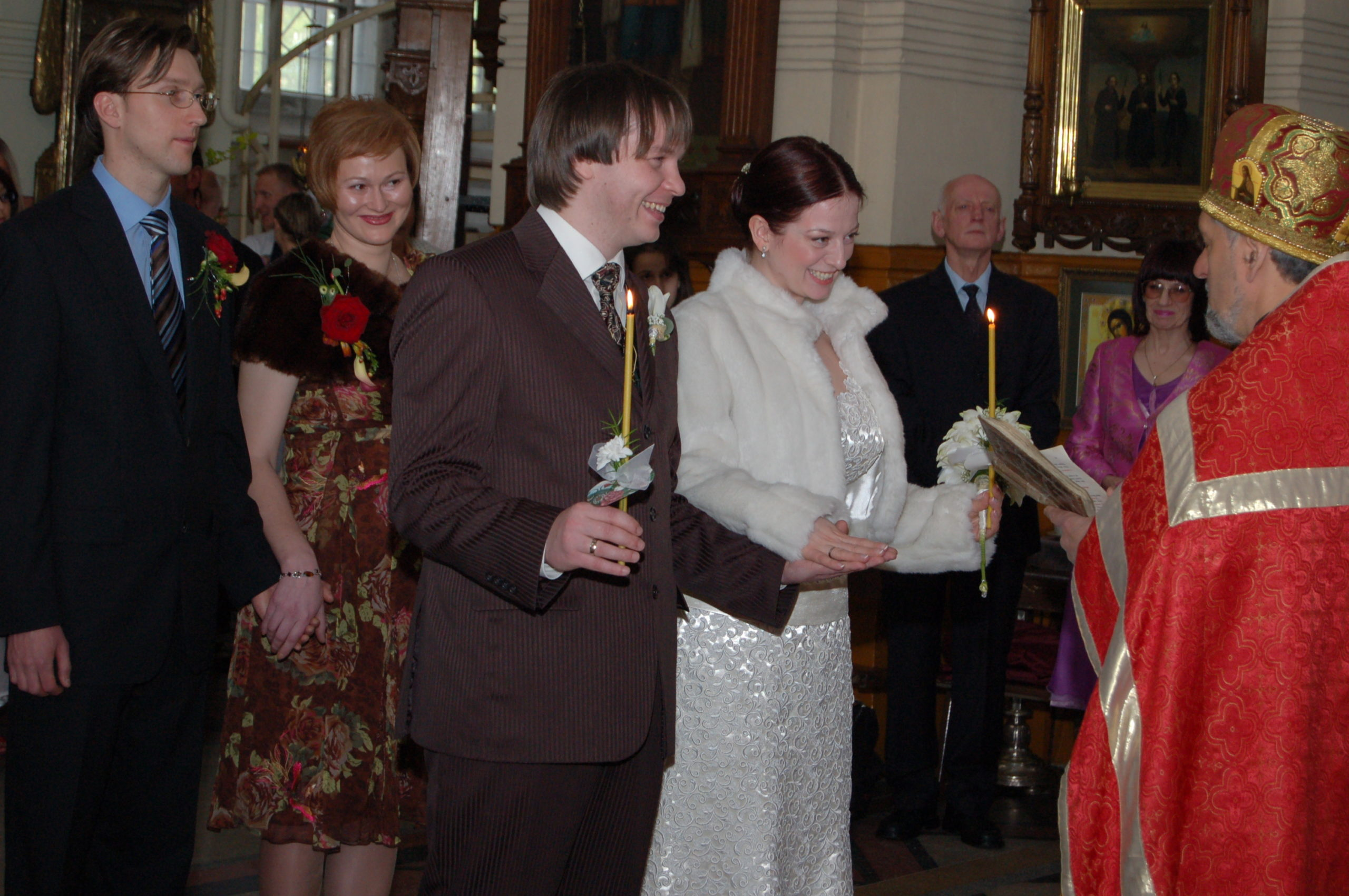 The priest faces the bride and the groom and reads, probably from the scripture