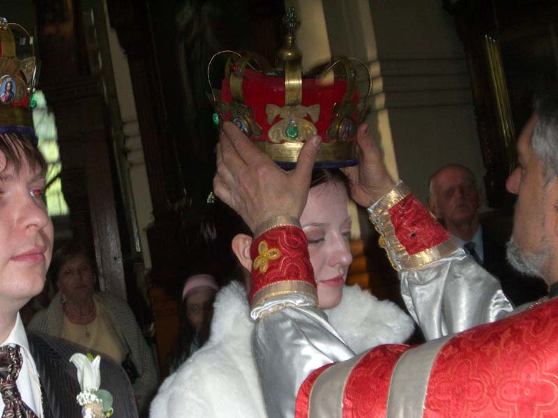 Priest puts crown on the bride's head