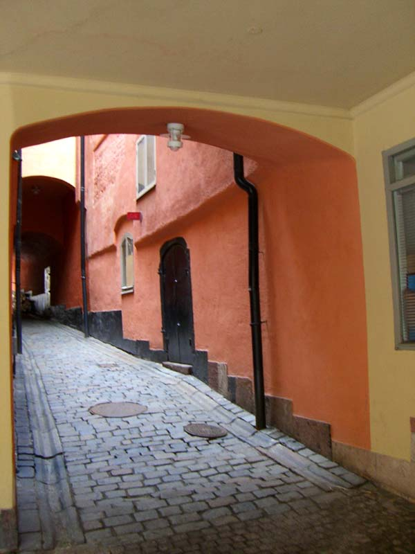 An arched passage leading to te round courtyard