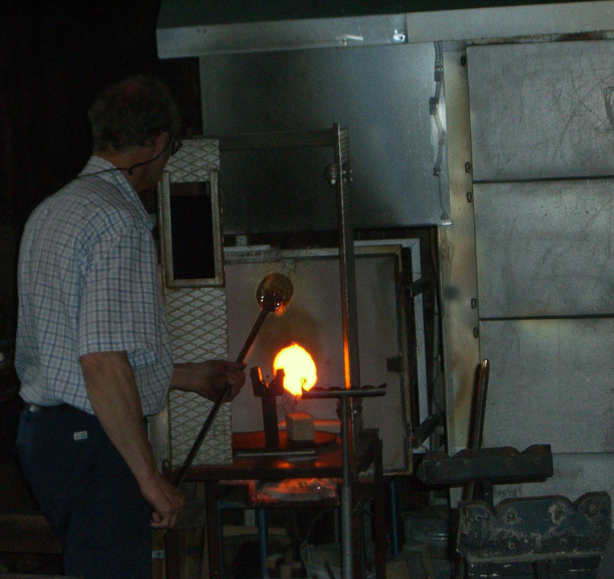 Glassmaker at Skansen takes glass out of the furnace