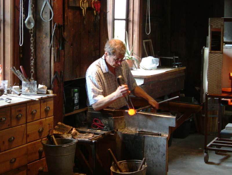 Glassmaker at Skansen shapes the glass bowl