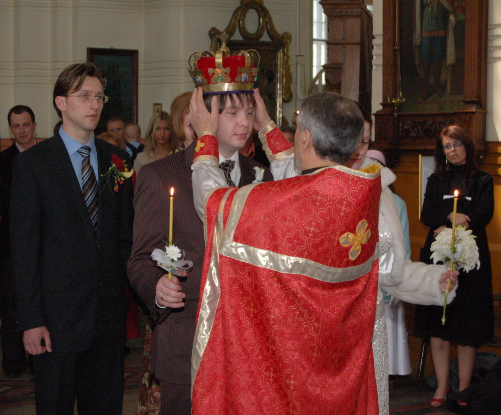 A priest puts a crown on groom's head