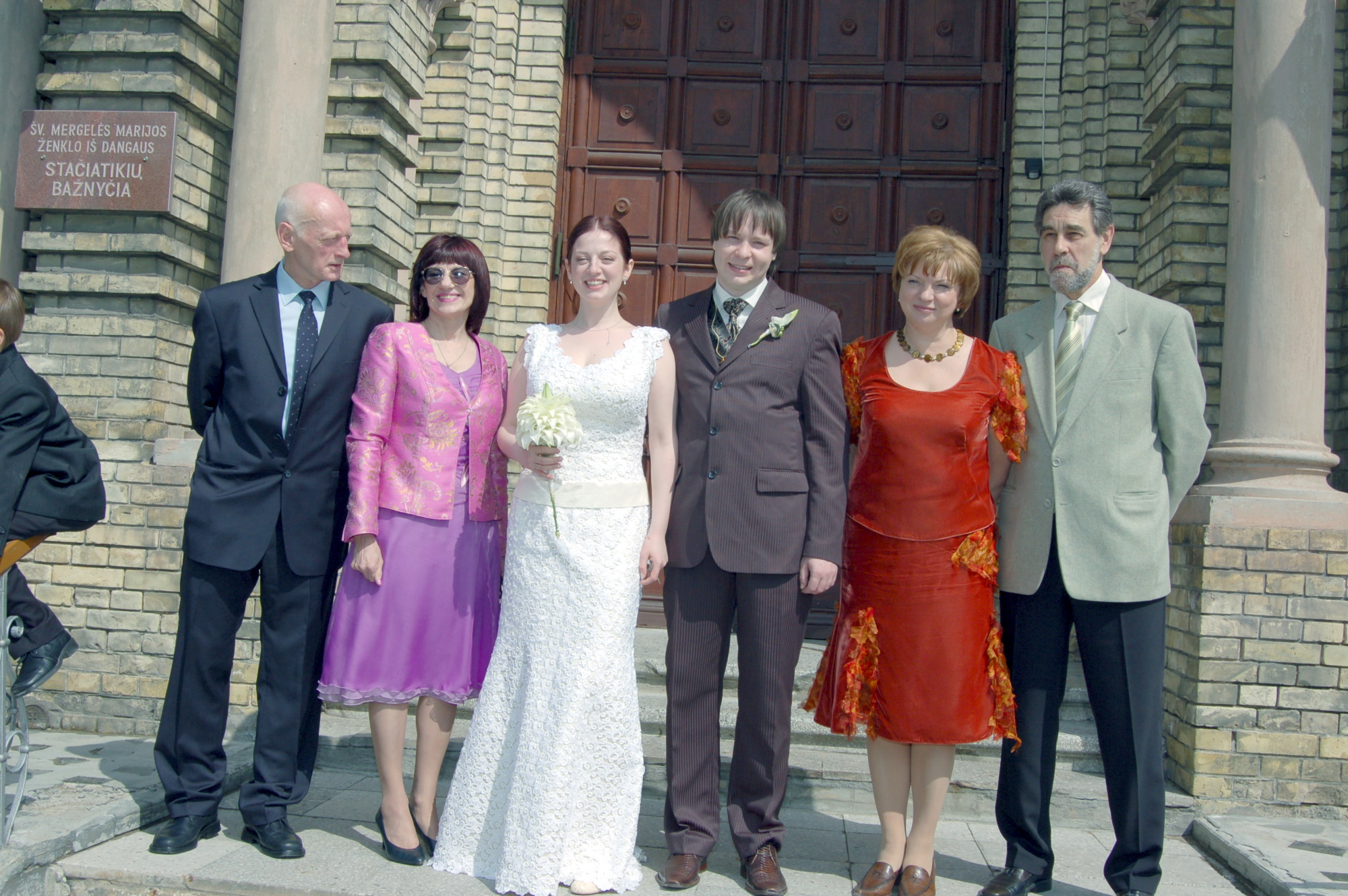 Newlyweds and their parents in front of church
