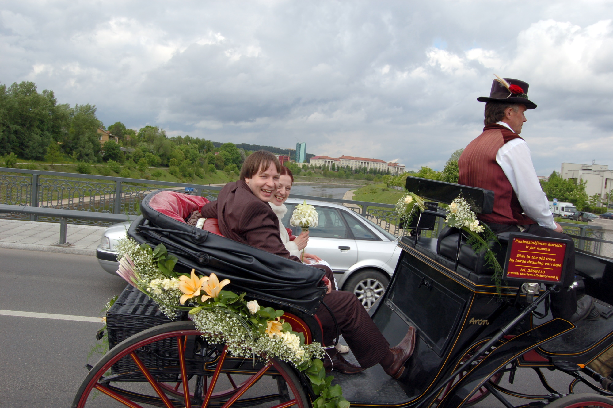 Newlyweds ride in a horse-drawn carriage over the bridge