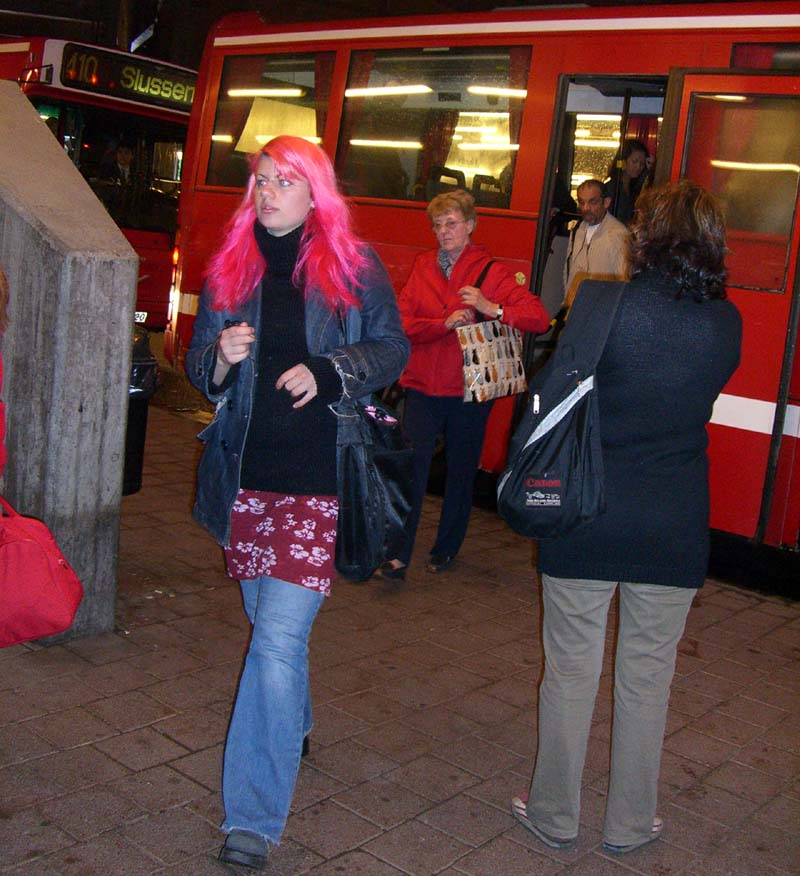 A person with magenta-colored hair in the subway in Stockholm