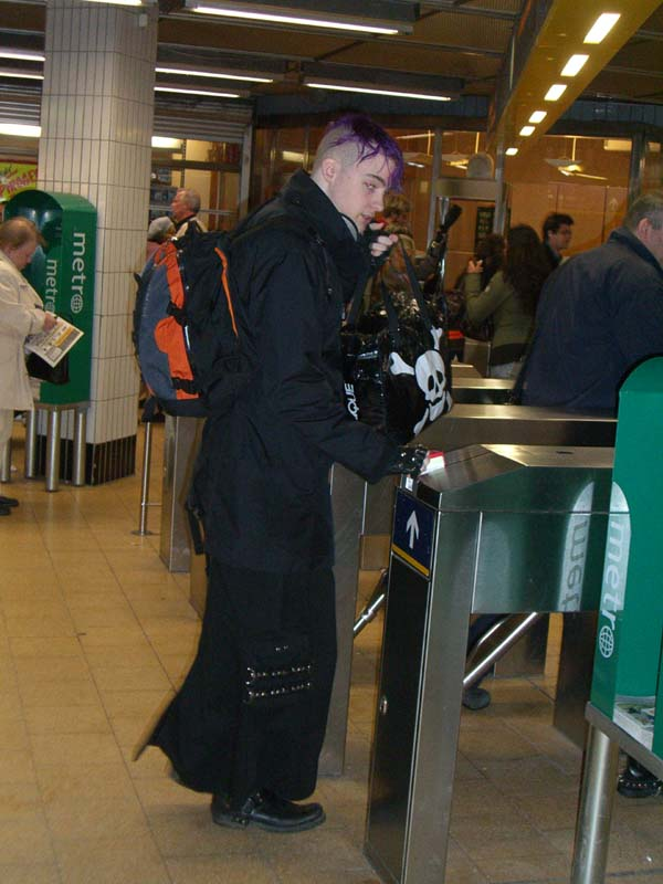 A person with purple hair and metal attire in the subway in Stockholm