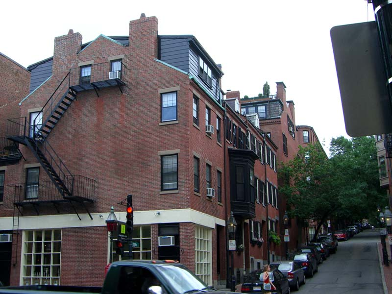 A corner of a street with red brick houses with a fire escape in Boston