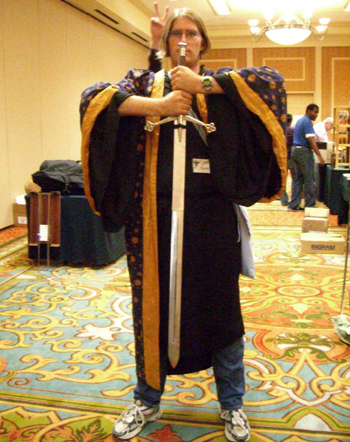 Con-goer in a starred cloak and a sword in the dealer room