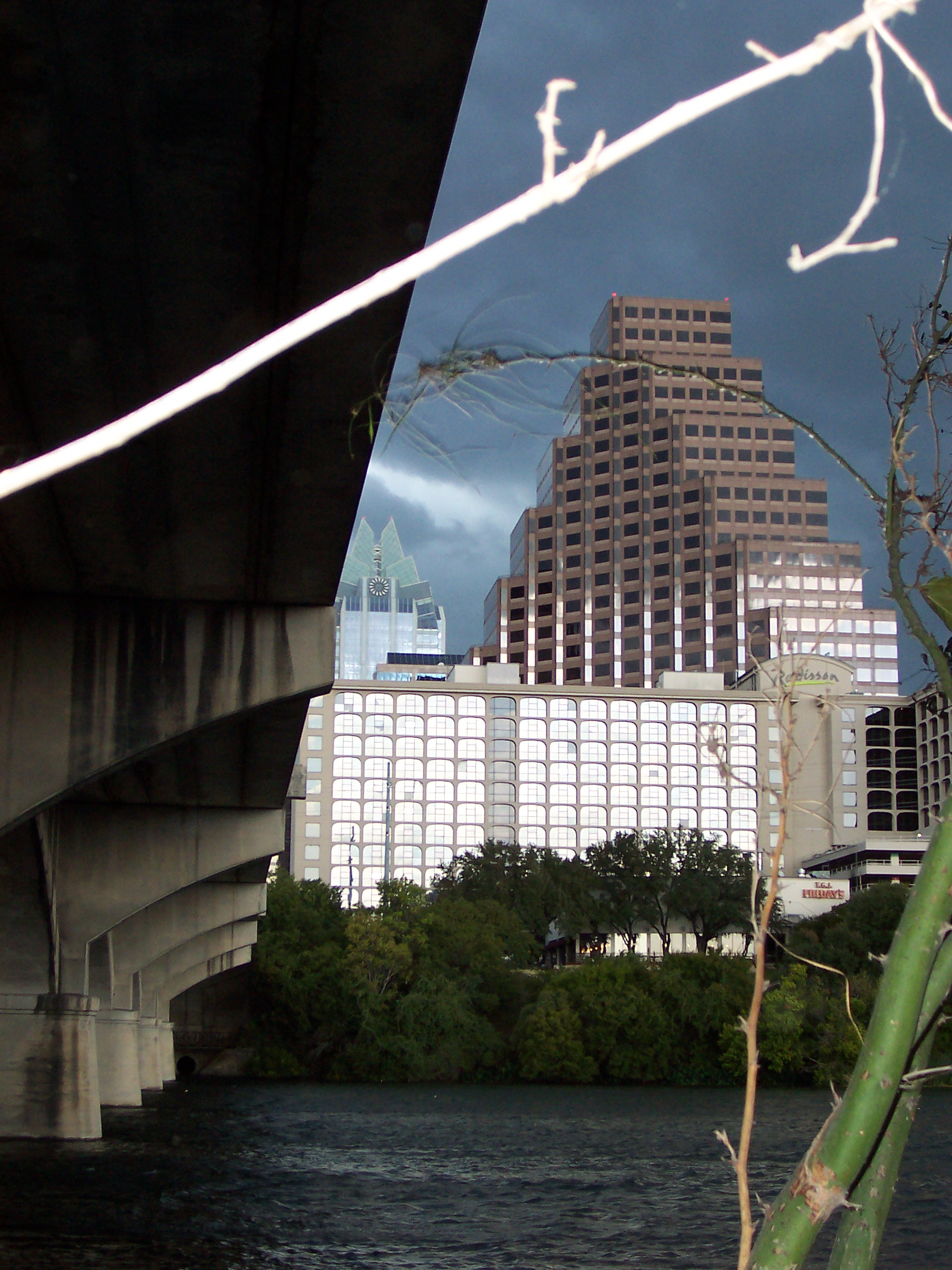 A triangular building in the Austin downtown, seen from under a bridge