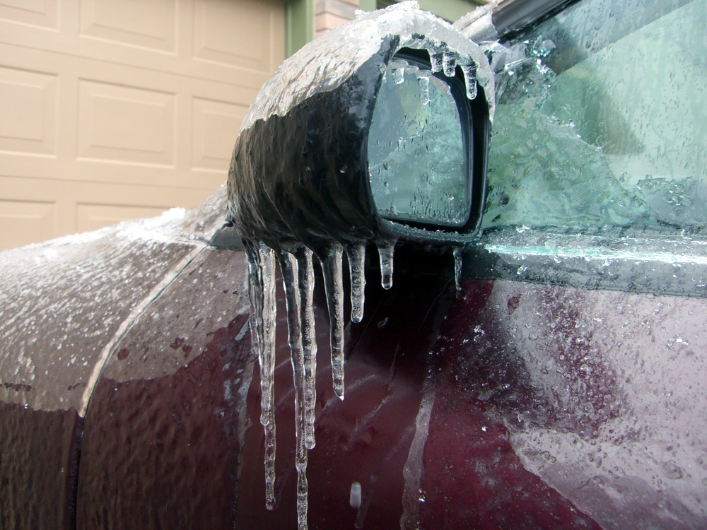 Car side mirror covered in icicles