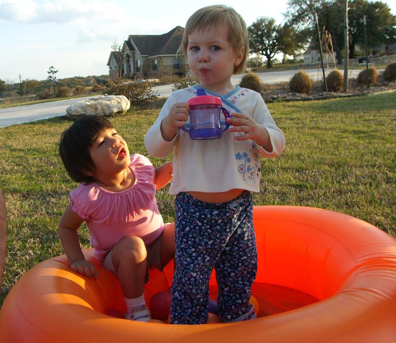 E (standing) with a friend in an inflatable pool