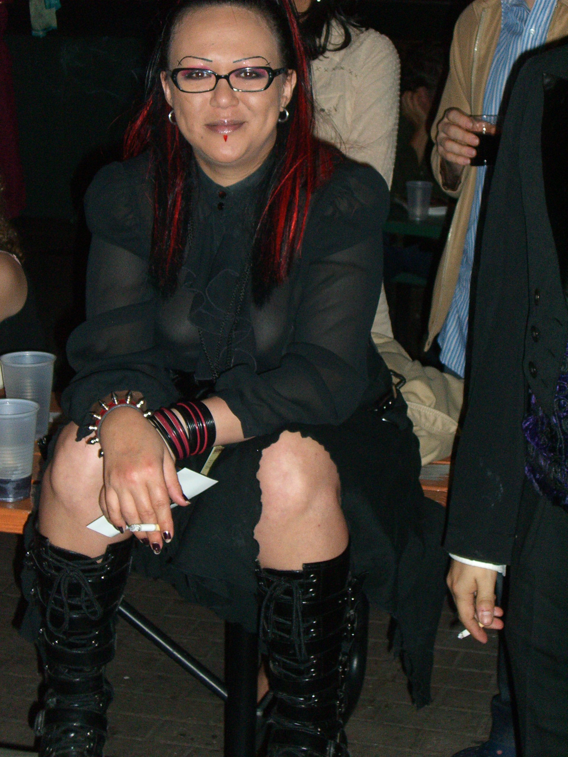 A costumer with long red-streaked hair and matching red-and-black bracelets.