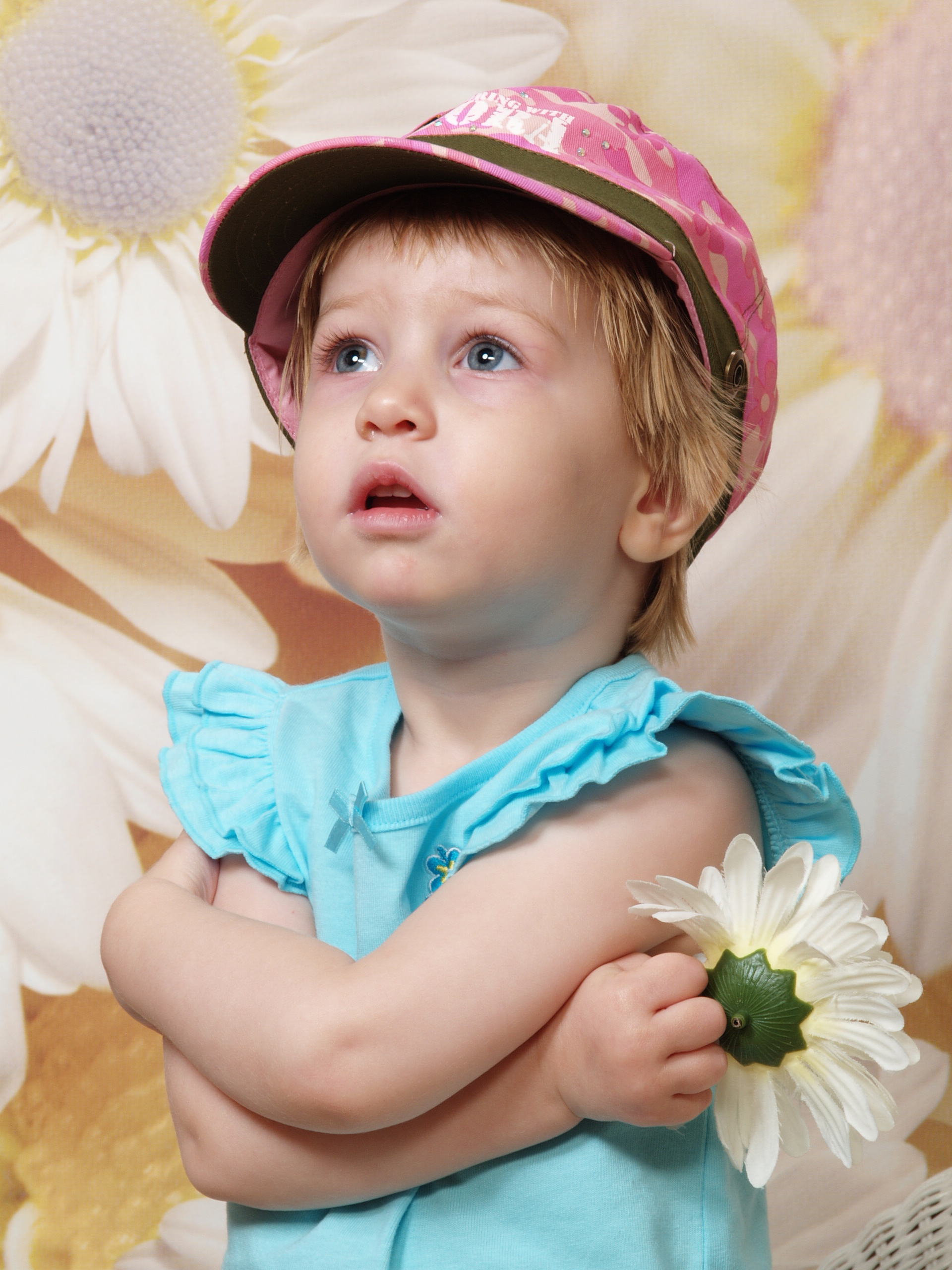 E in front of giant daisies with a hat, looking up, May 2007
